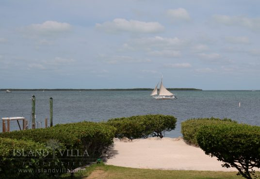 sail boat passing by the bay front property