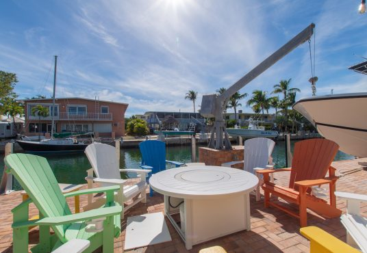 colorful dockside chairs with fire pit on canal front patio