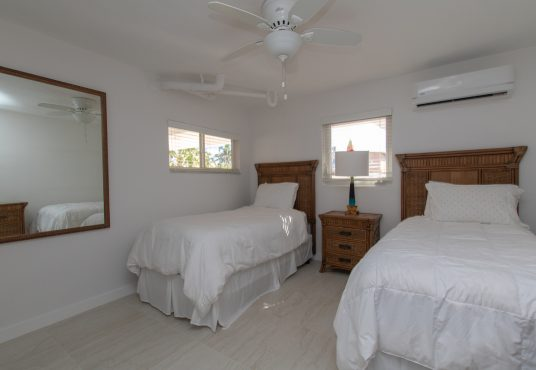 twin beds with clean crisp white linen and rattan furniture