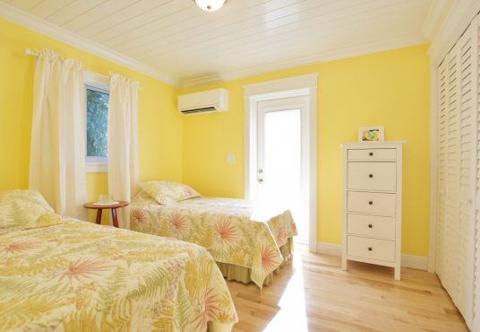 sunshine yellow bedroom with twin beds and lots of natural sunlight
