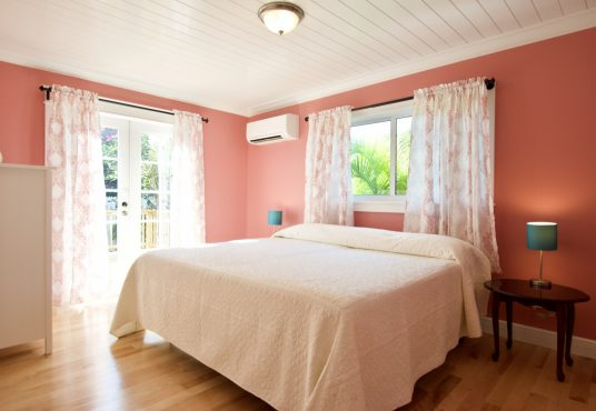 coral pink bedroom with king size bed and crisp white linens