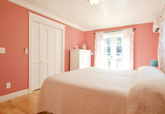 coral pink bedroom with french doors and lots of natural sunlight