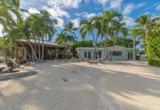 sand and palm trees complete the backyard of this charming beach house in islamorada florida keys