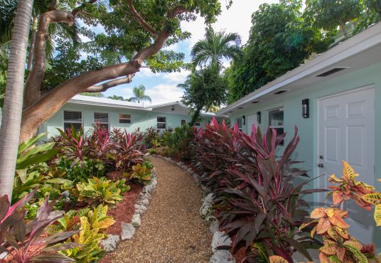 lush tropical landscaping greets you as you enter the front of beach house estate vacation rental